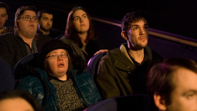 A scene from Sanctuary shows care worker Tom in the cinema with the group