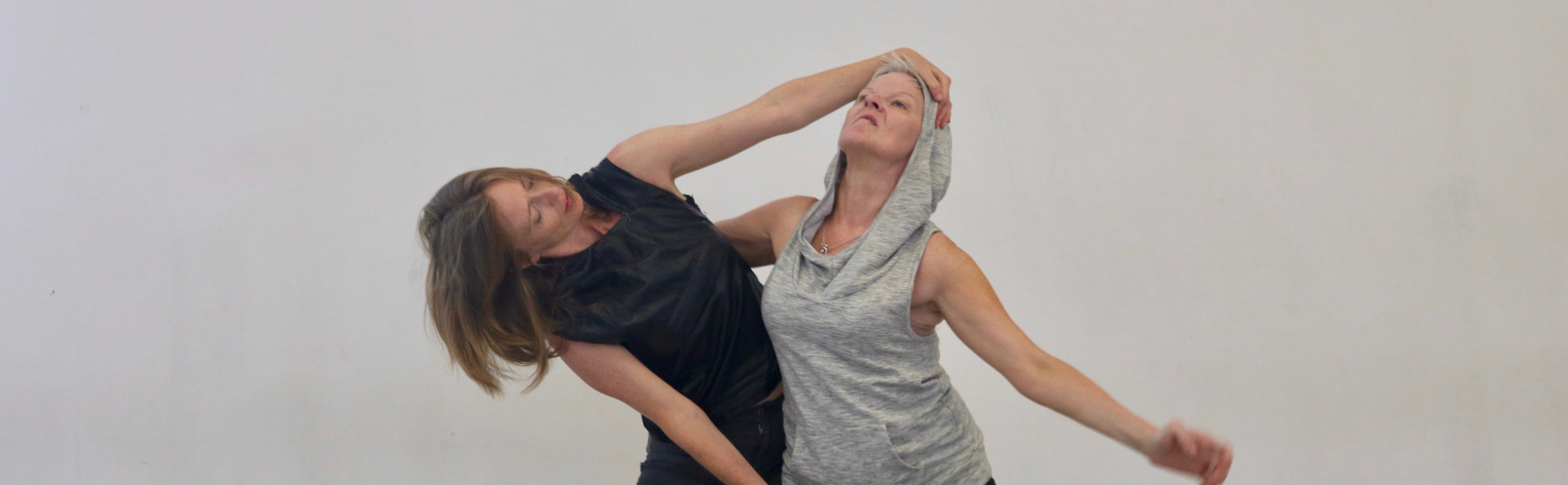 One woman in black and one woman in grey dancing with a grey background