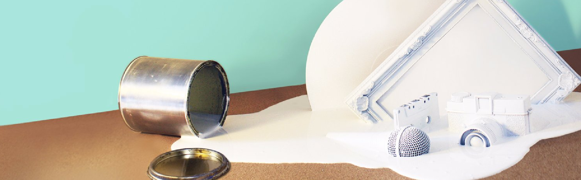 Tipped over tin of white paint with a paint-covered circle, picture frame, cassette tape, microphone and a vintage camera, on a wooden table with a bright turquoise background.