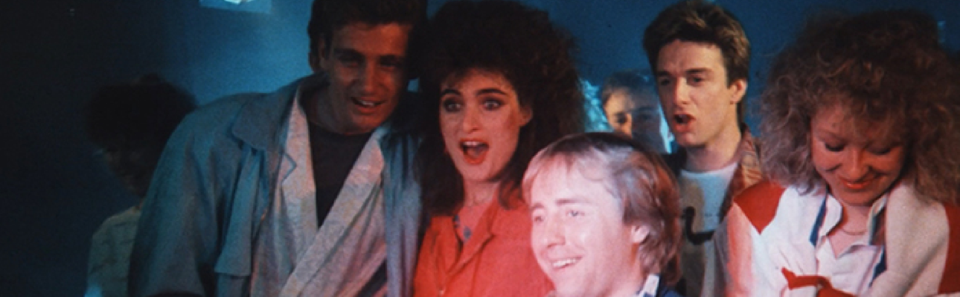 A group of four people smiling dressed in 80's style clothing and hairstyles.
