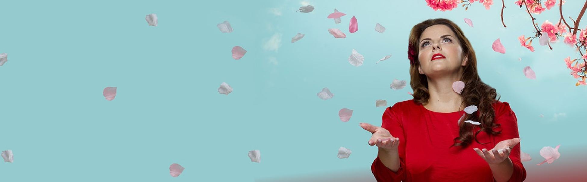A woman dressed in red looking upwards with her palms open to catch cheery blossom petals as they're falling.