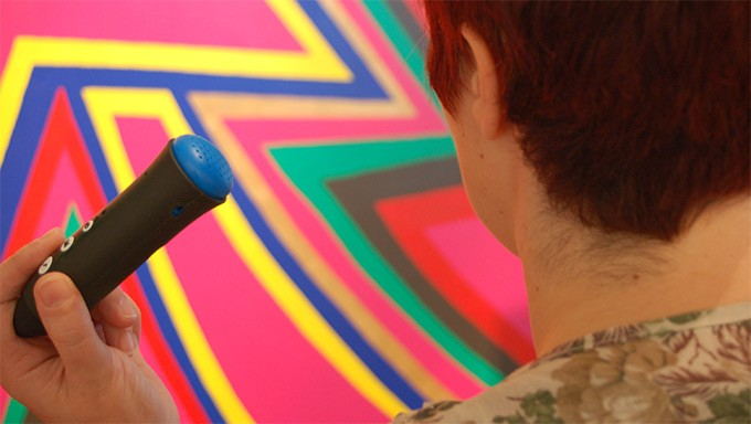 An audience member using audio description on a Discovery Pen at a visual art exhibition
