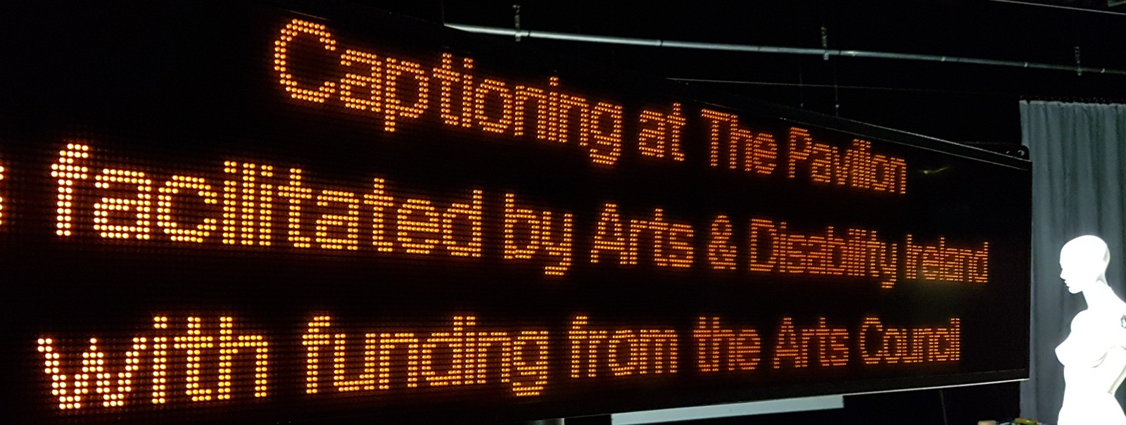 A captioning unit displaying text in orange LED lights. The text reads: Captioning at The Pavilion Theatre is facilitated by Arts & Disability Ireland with funding from the Arts Council.