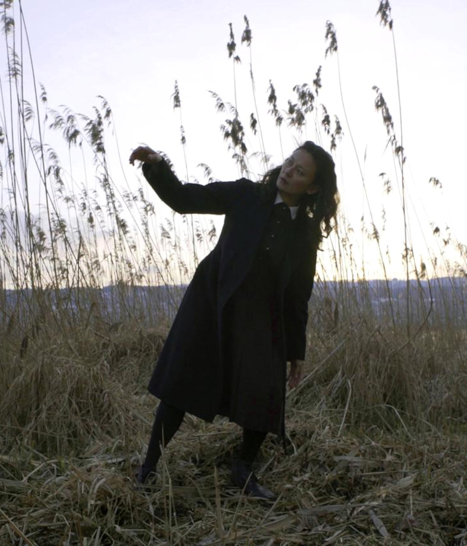 A still from the film Horrible Creature. A woman with dark shoulder length hair wearing a dark dress and coat dances in a field. The light is soft and pink on the horizon. She is surround by tall crops.
