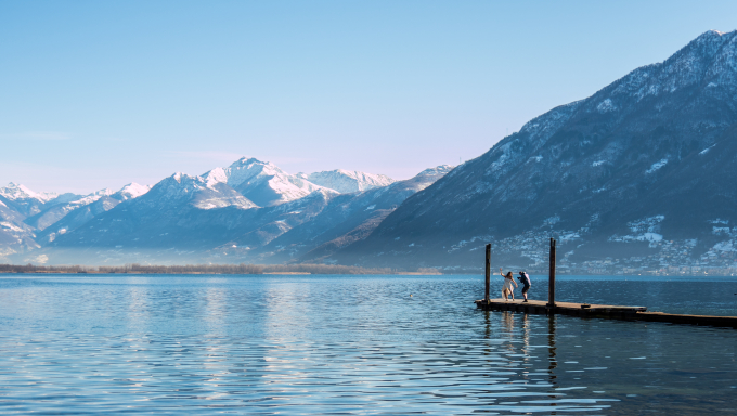 A photograph of the filming of Horrible Creature. A woman dances in front of a cameraman on a jetty. The jetty juts out into a lake that is surrounded by snow-capped mountains.