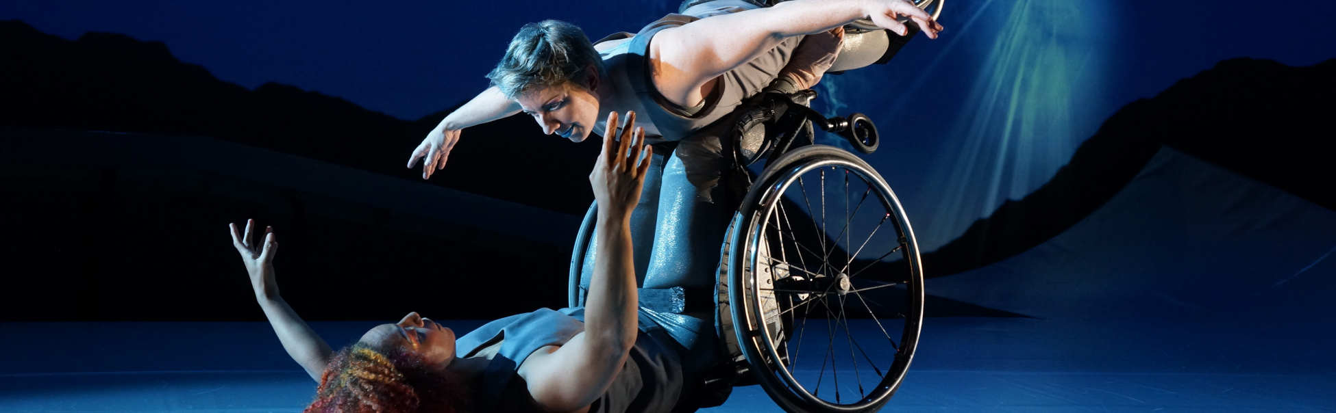 Laurel Lawson, a white woman, is flying in the air as Venus with arms spread wide and wheels spinning, supported by Alice Sheppard. Alice, a light-skinned Black woman, is lifting from the ground below as Andromeda.