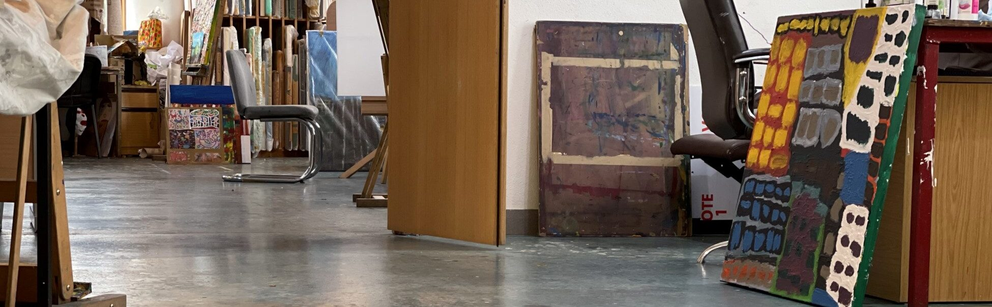The KCAT studio floor, with artists racks built into the walls, bare concrete floors with canvases littered around